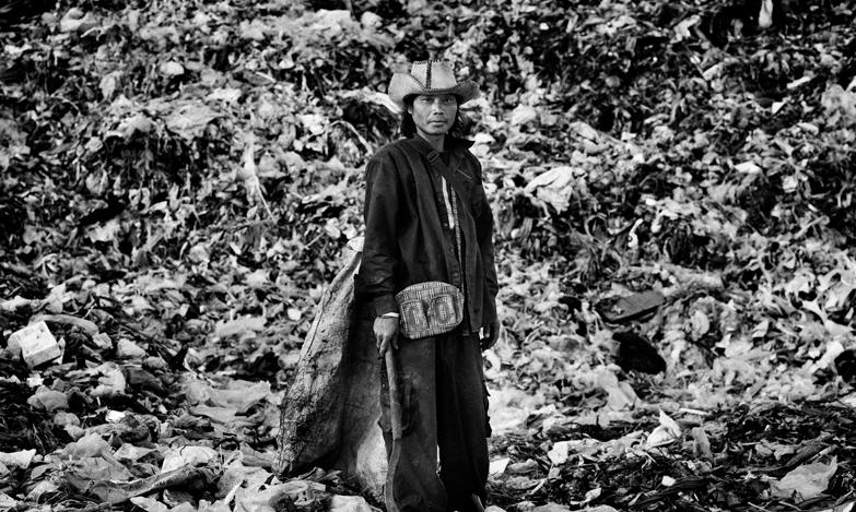 The Recyclers | La vita dei migranti birmani nella discarica di Mae Sot - © Vincenzo Floramo Secondo le statistiche del governo, ci sono almeno due milioni di cittadini birmani che lavorano in Thailandia, almeno tre quarti di loro sono illegali. Migliaia di cittadini del Myanmar (ex Birmania) attraversano il confine per fuggire da uno dei regimi più crudeli e ingiusti che esistano tuttora nel mondo. Lungo il confine tra Thailandia e Myanmar, la città di Mae Sot è diventato un rifugio per molte famiglie di immigrati birmani, anche illegali. Parecchi immigrati vivono in una grande discarica appena fuori Mae Sot, circa cinquanta famiglie che abitano in capanne di bambù costruite su montagne di rifiuti. Vivono recuperando materiali riciclabili che poi rivendono. Ma i rifiuti arrivano alla discarica dopo essere già passati attraverso un doppio processo di selezione, il che rende ancor più difficile recuperare materiale riutilizzabile, e quel che resta permette loro di guadagnare circa 100 baht (2,5 euro) al giorno. Foto documentario del fotografo italiano Vincenzo Floramo