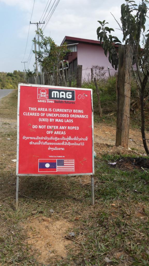 Il cartello, a lato di una strada in provincia di Xiangkhoang, avverte che una squadra del Mine Advisory Group sta lavorando nella zona. Il team utilizza esplosivi per far esplodere bombe inesplose che si trovano nella zona e gli abitanti sono invitati a non avvicinarsi. Foto di John Dennehy