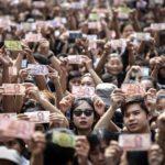 Thailandesi  in strada mostrano banconote con l'immagine di Re Bhumibol Adulyadej a Bangkok, 14 ottobre 2016.