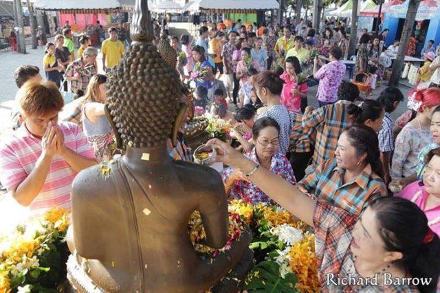 Donne donano fiori e versano acqua ad una statua del Buddha in occasione del festival del Songkran, Thailandia, aprile 2017